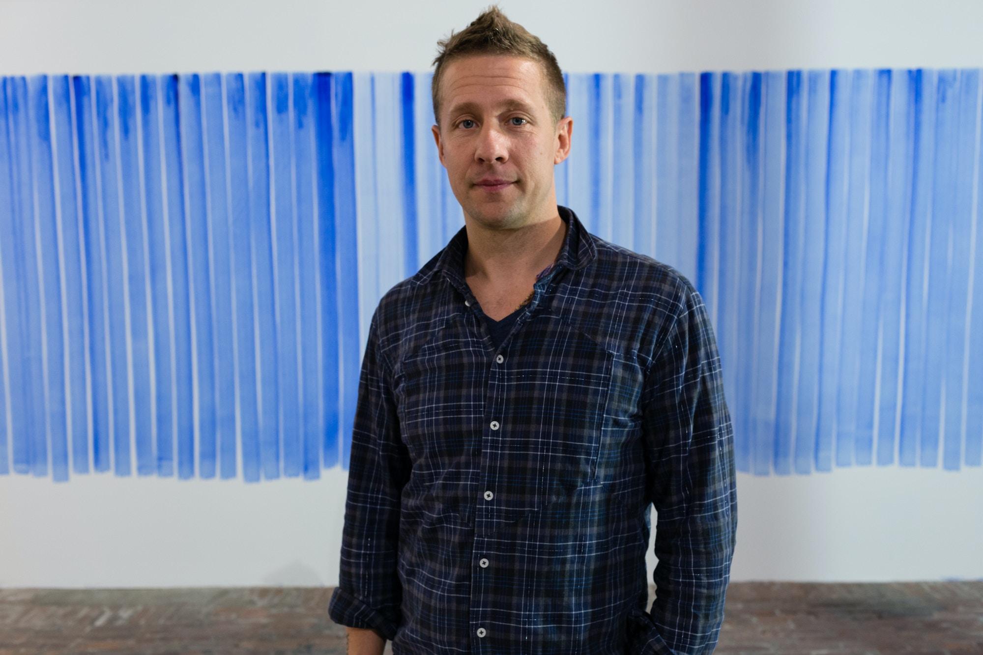 Kunsteneren Jeppe Hein foran en hvit vegg med blå penselstrøk på.