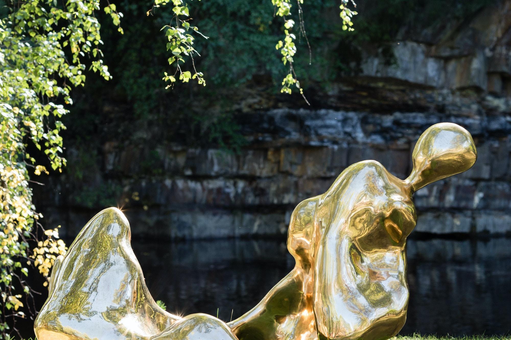 Bronzeskulptur ligger på bakken ved kanten av Randselva.