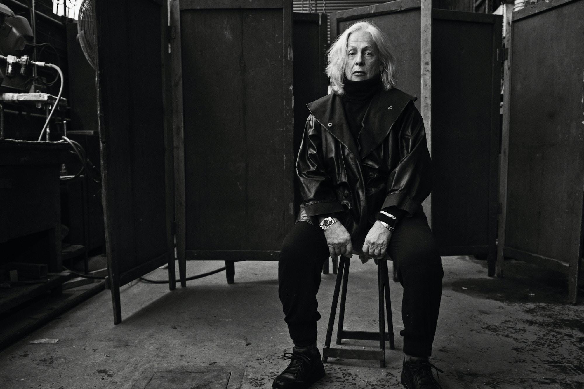 Svart hvitt portrett av Lynda Benglis, sittende på en stor.