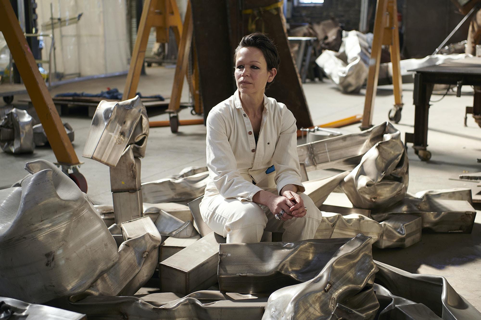 Carol Bove portrett. Bove sitter i verksteded sitt omgitt av bente jernmaterialer.