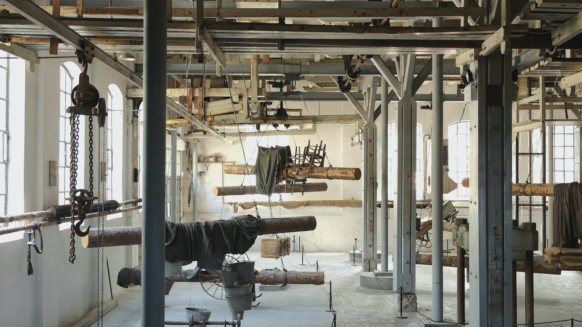 Bildet viser et gammelt fabrikkloakle som i dag er omgjort til et industrimuseum. Utsmykket med en installasjon som blant annet består av tømmerstokker og stoler.