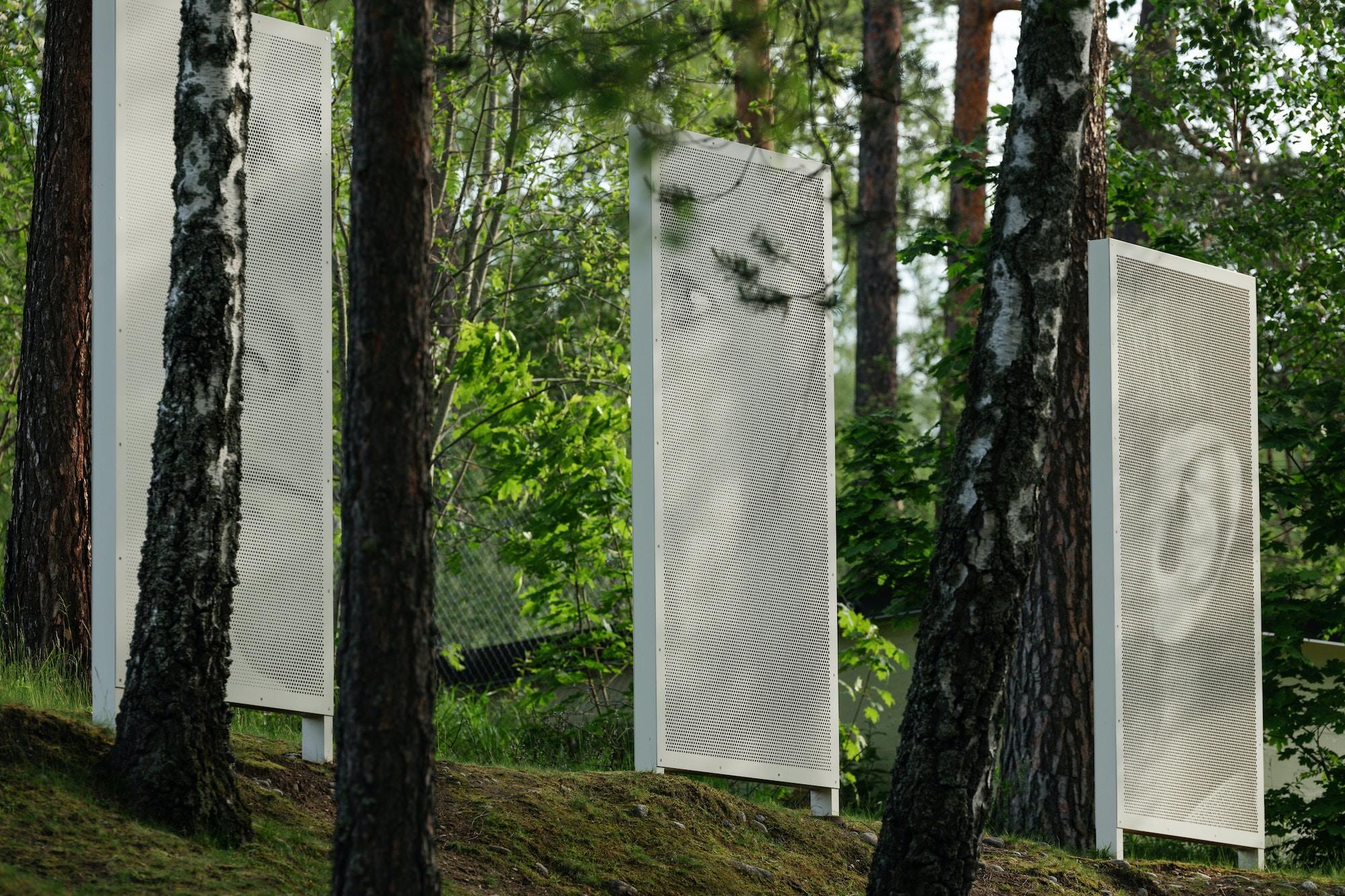 Skulptur plassert i grønn natur. Tre plater med portrett av Christen Sveaas.