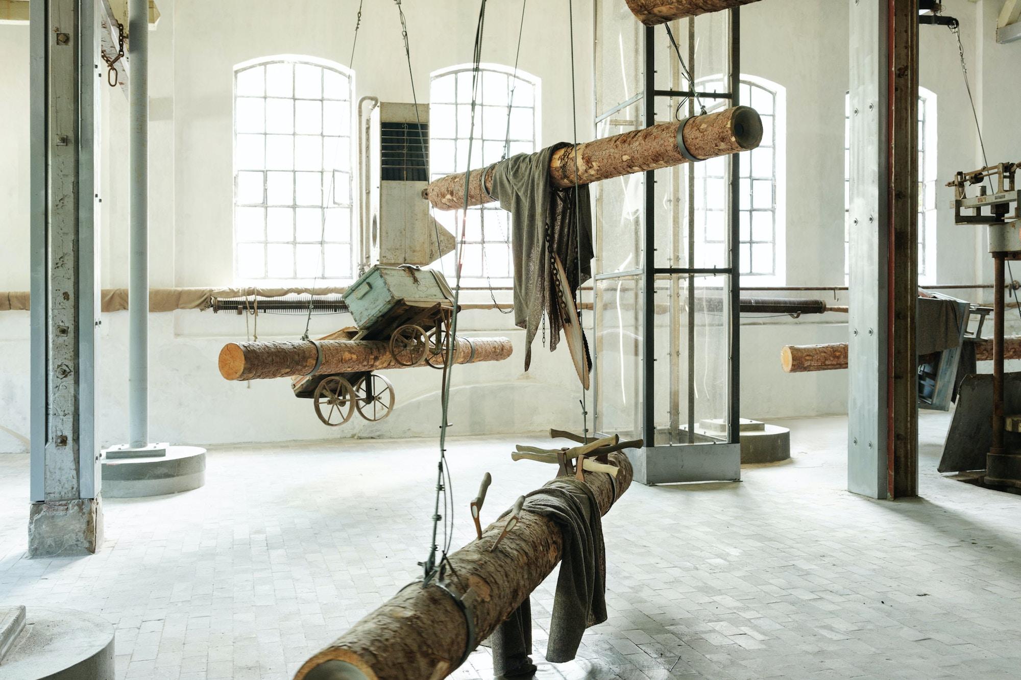 Kunstinstallasjon. Tømmerstokker henger fra taket i en gammel fabrikkhall.