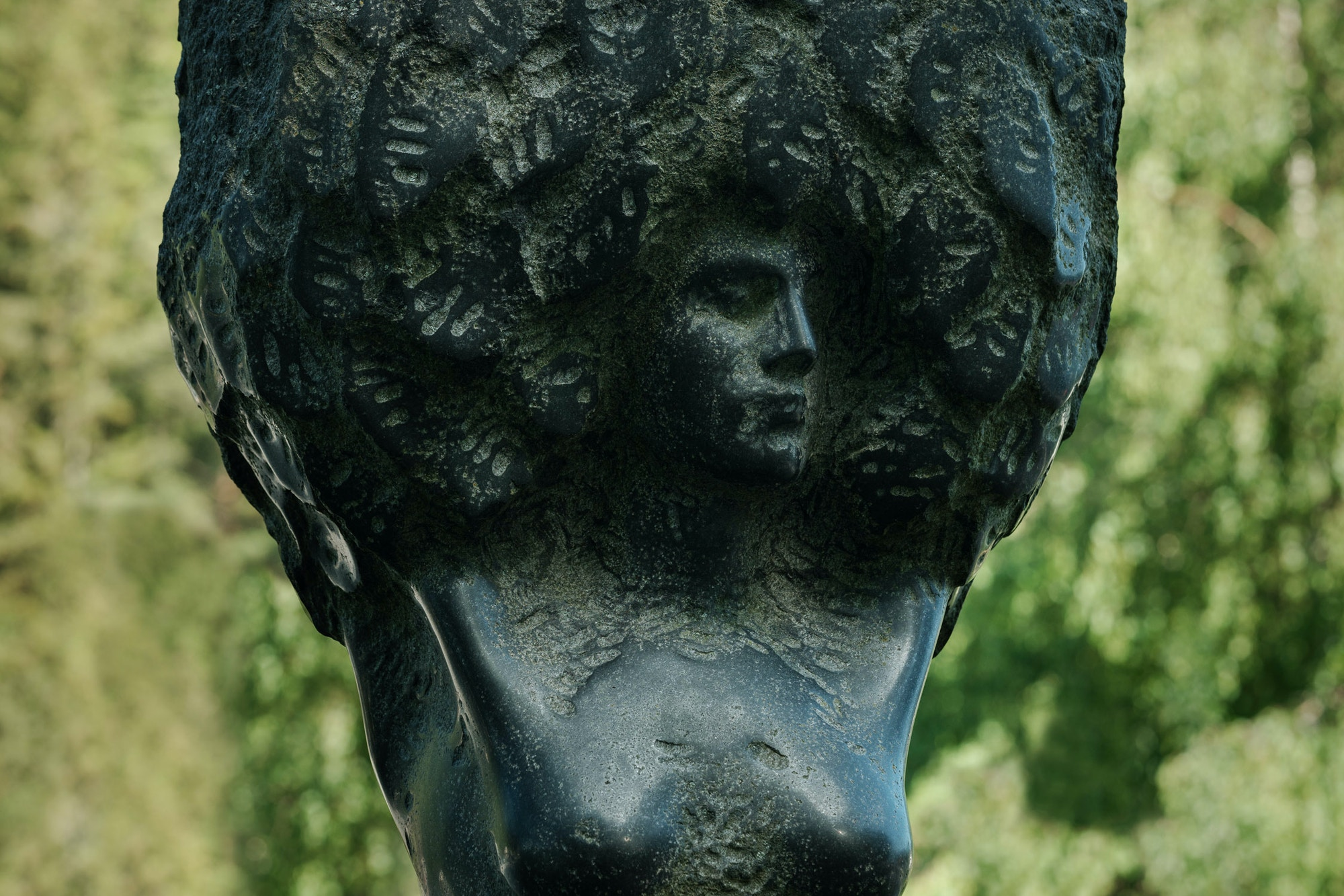 Statue of a woman. Torso. Big hair.