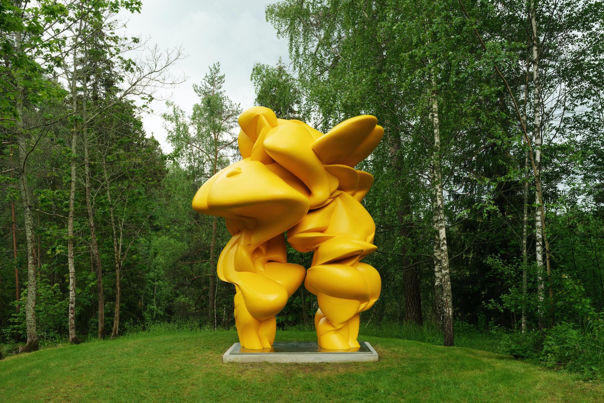 En stor gul skulptur står i skogen.