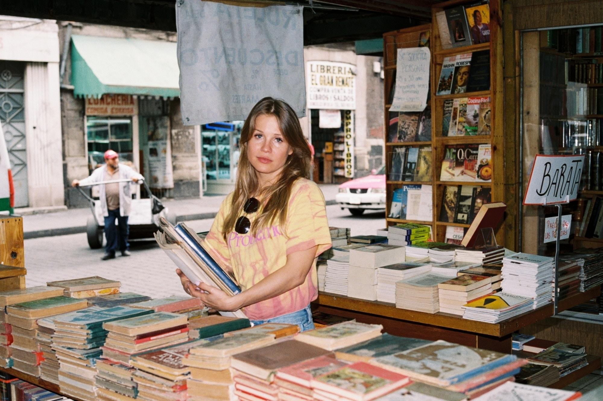 Portrett av kunstner Ida Ekblad. Jente med langt lyst hår holder bøker i en gammel bokhandel.