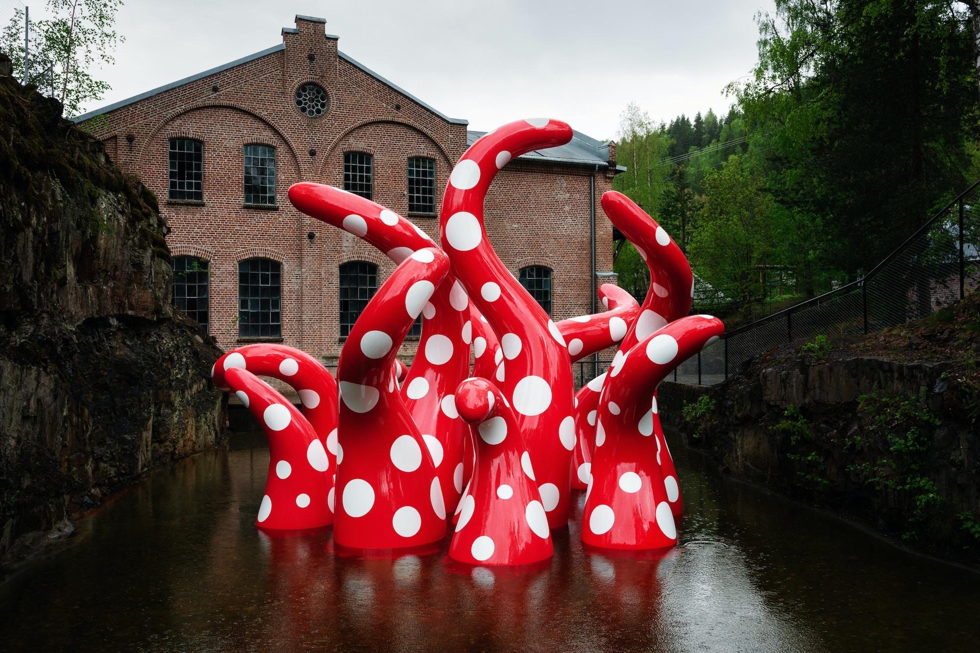 Skulptur av Yayoi Kusama med åtte røde blekksprutliknene armer med hvite prikker stiger opp av vannet. I bakgrunnen ser man det gamle tresliperiet.