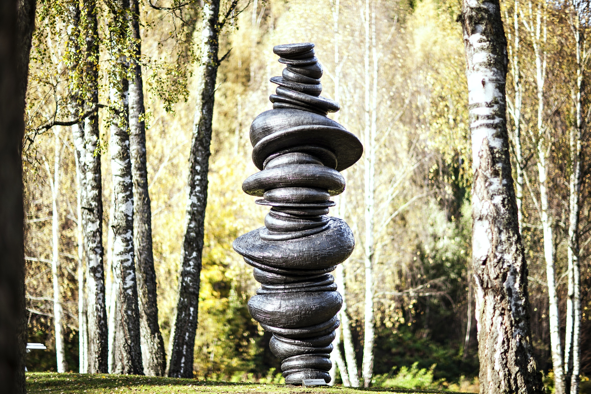 Tall black sculpture, made up of round stones on top of each other.