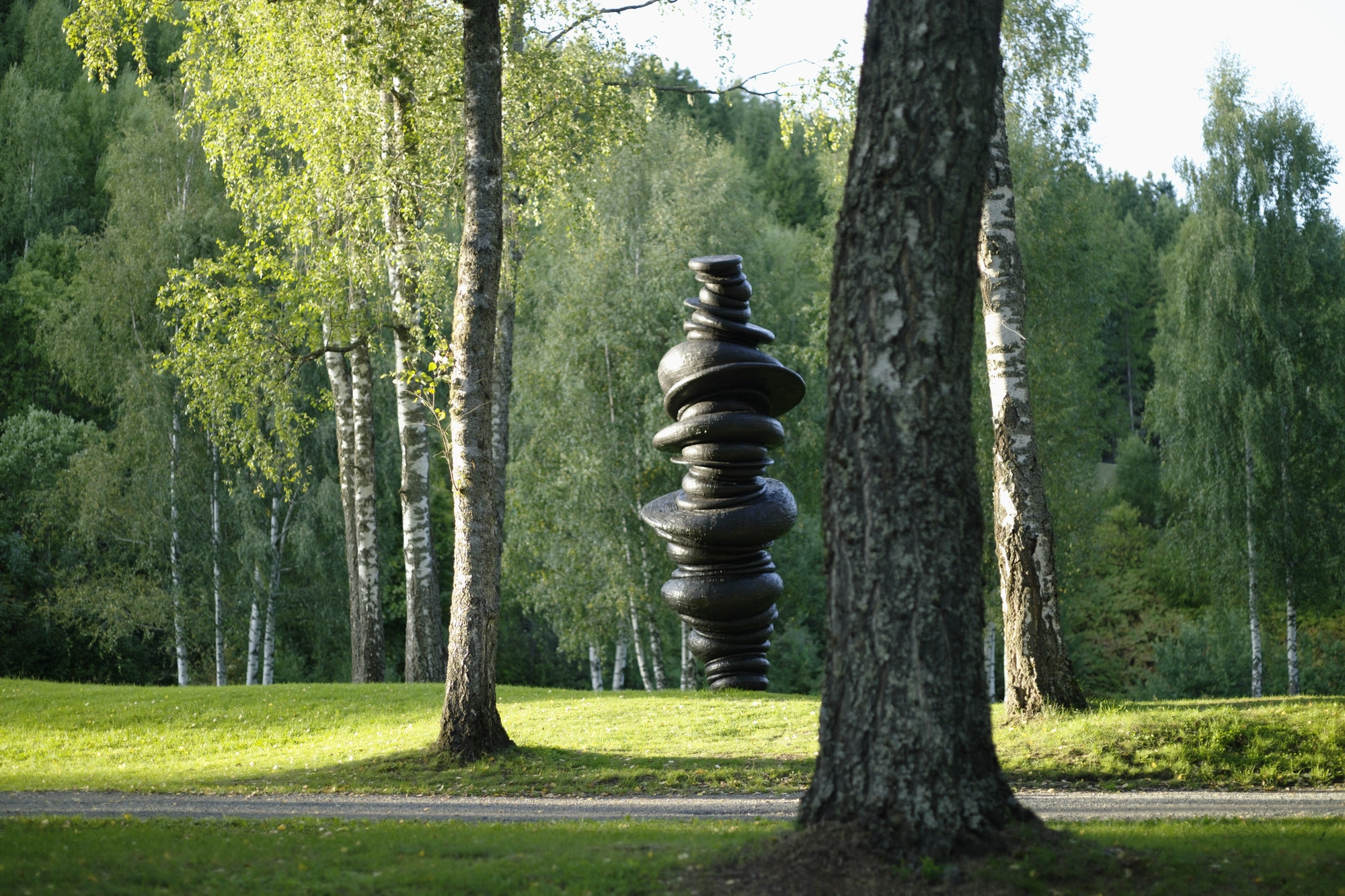 Sculpture, black, stones placed on top of each other. Nature, green.