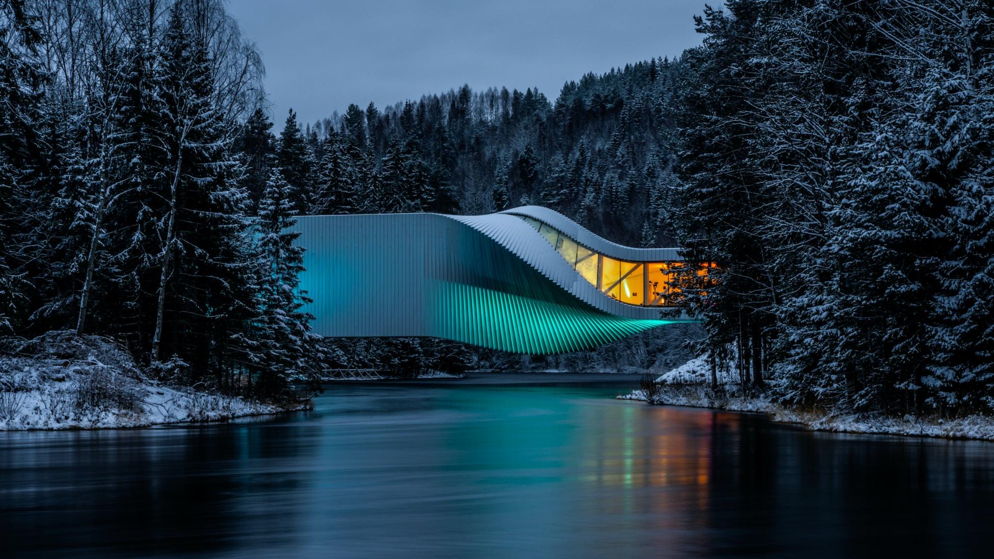 Museumsbygget The Twist i vinterdrakt. Blått lys ute, gult lys inne i bygget. Snø på trærne rundt.